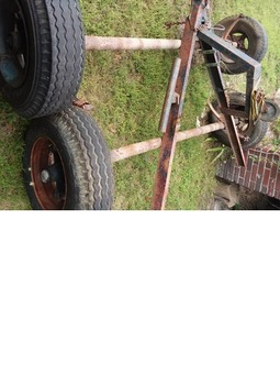Two trailer axles with tires and rims and tongue
